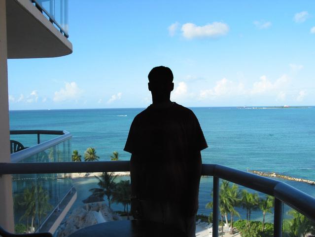 Muž pozerá z balkóna, more