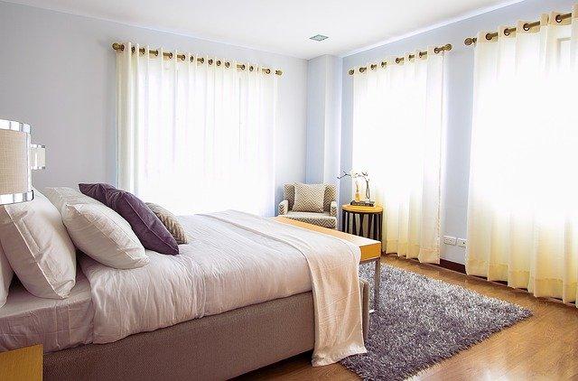 Spálňa s malou posteľou, veľkými oknami a závesmi