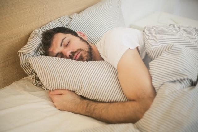 Muž spí zakrytý paplónom v posteli
